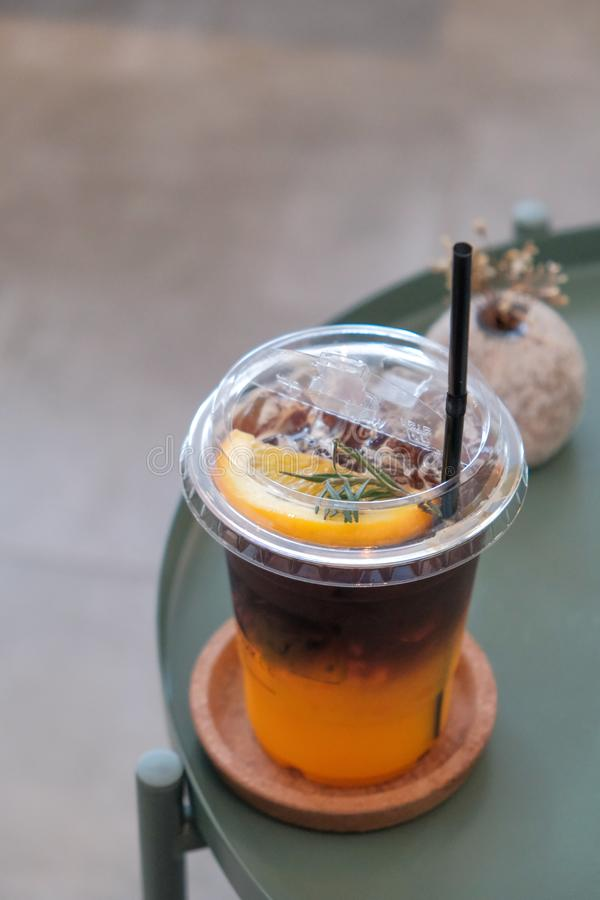 Orange juice in the bottom and dark coffee and orange slices  on the top in the glass. Orange juice in the bottom and dark coffee and  orange slices  on the top stock images