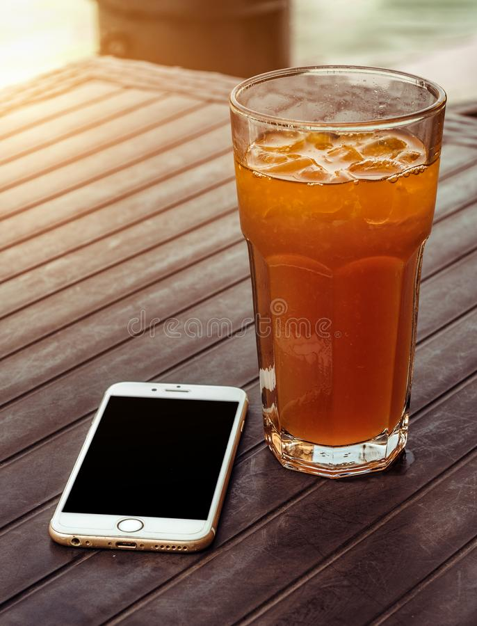 Orange Juice in Clear Drinking Glass Besides Gold Iphone 6 on Brown Wooden Table stock image