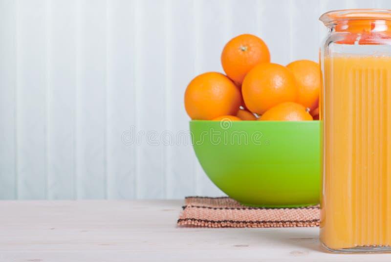 Orange juice beside delicious ripe oranges on the table royalty free stock image
