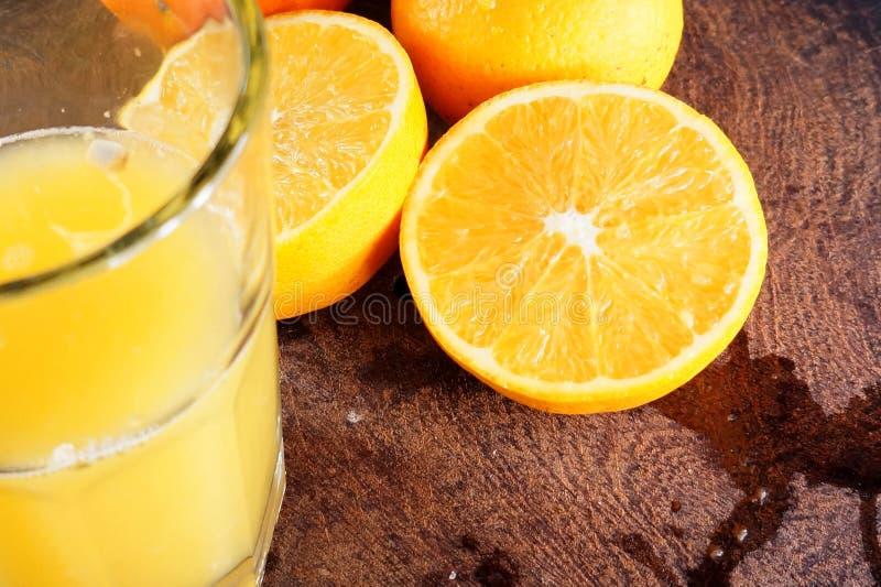 Orange juice. A fresh made orange juice in a glass. Beside a few orange, one of them cut in half stock images