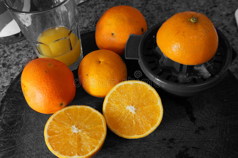 Orange juice. A fresh made orange juice in a glass. Beside a few orange, one of them cut in half. Backgrounf in black and white royalty free stock photos