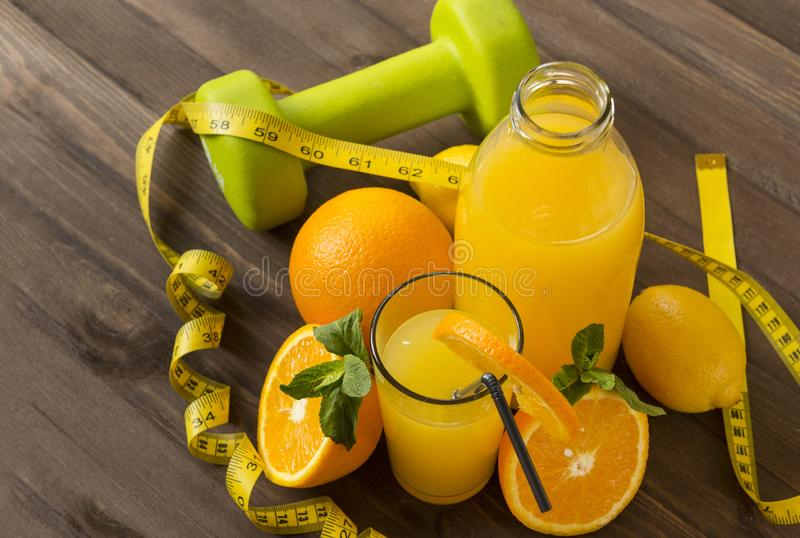 Orange juice in glass and bottle, fresh oranges, measuring tape, green dumbbell on wooden background royalty free stock photos