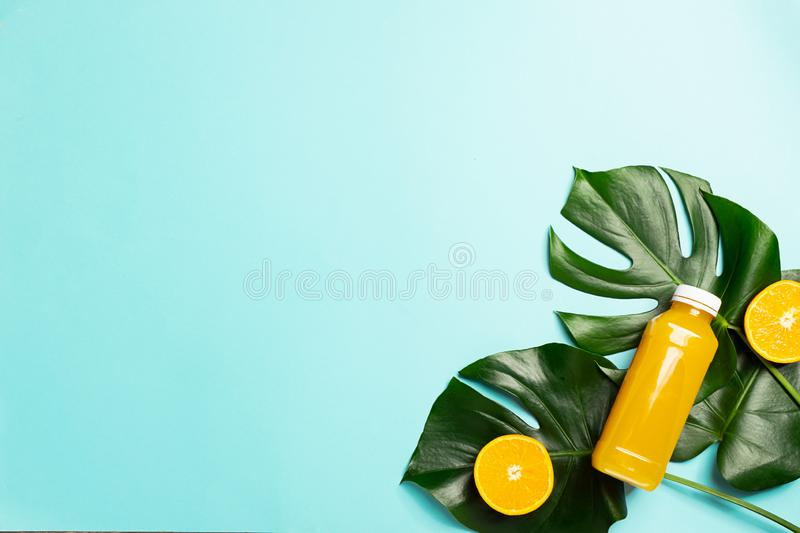 Orange juice in glass bottle on a sheet of a tropical plant bright blue background. Healthy eating concept. Minimalism. stock photos
