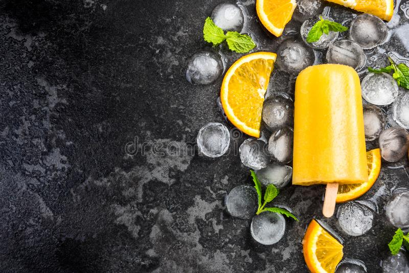 Orange juice homemade popsicle over ice. Mint and fresh fruits background cold colorful concept cool copyspace dark delicious dessert flat lay flavor flavored royalty free stock images
