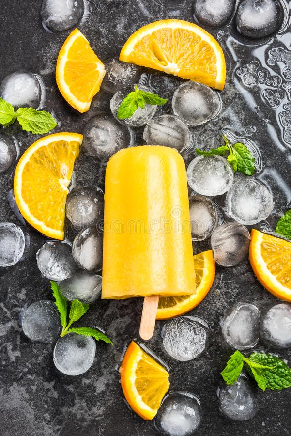 Orange juice homemade popsicle over ice. Mint and fresh fruits background cold colorful concept cool copyspace dark delicious dessert flat lay flavor flavored royalty free stock image