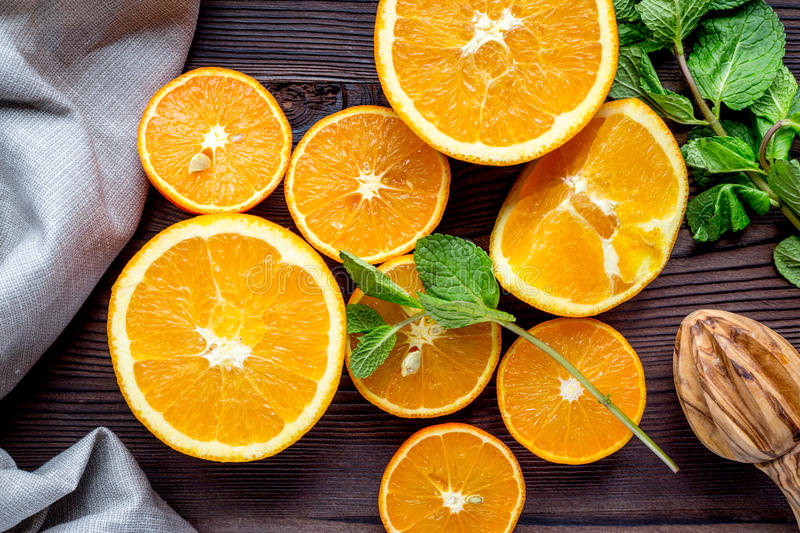 Orange juice with mint squeezing on wooden kitchen background top view royalty free stock photos