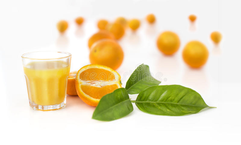Orange juice with oranges and leaves in the background. Still life with a variety of fruit and a glass of drink royalty free stock images