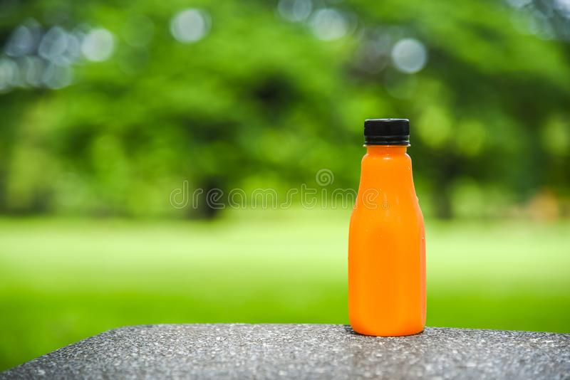 Orange juice in plastic bottle on green natural background.  royalty free stock photos