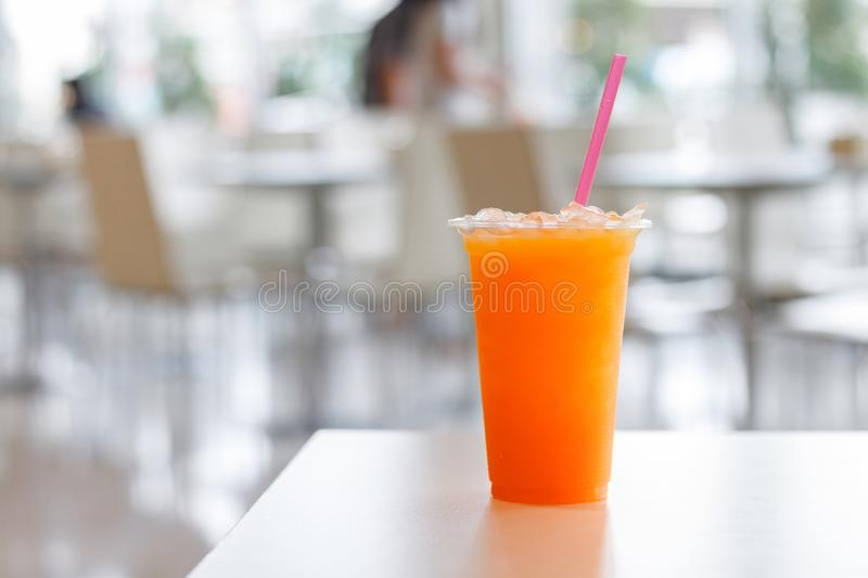 Orange juice in plastic glass and tube on white table background. Vitamin C drink for healhty stock image