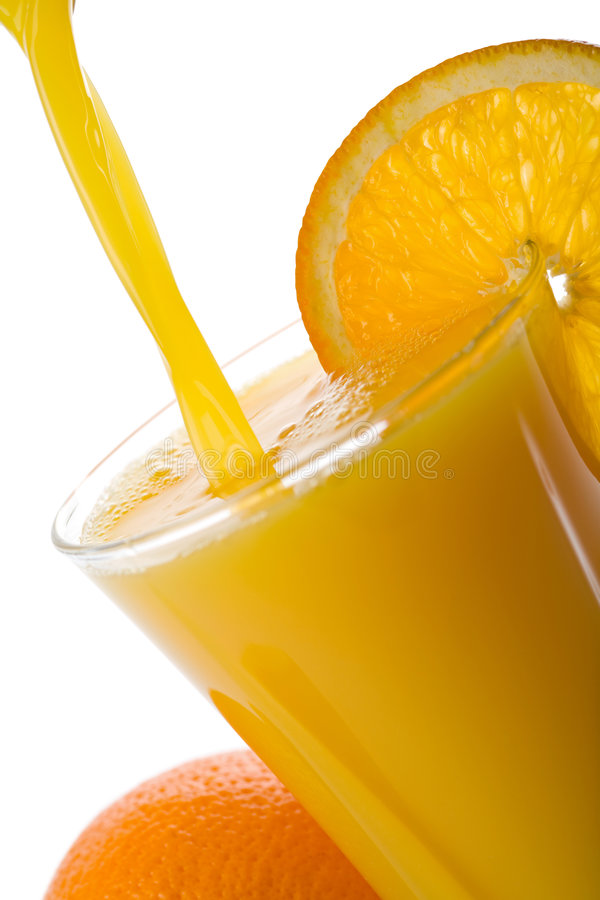 Orange juice pouring into glass isolated royalty free stock image