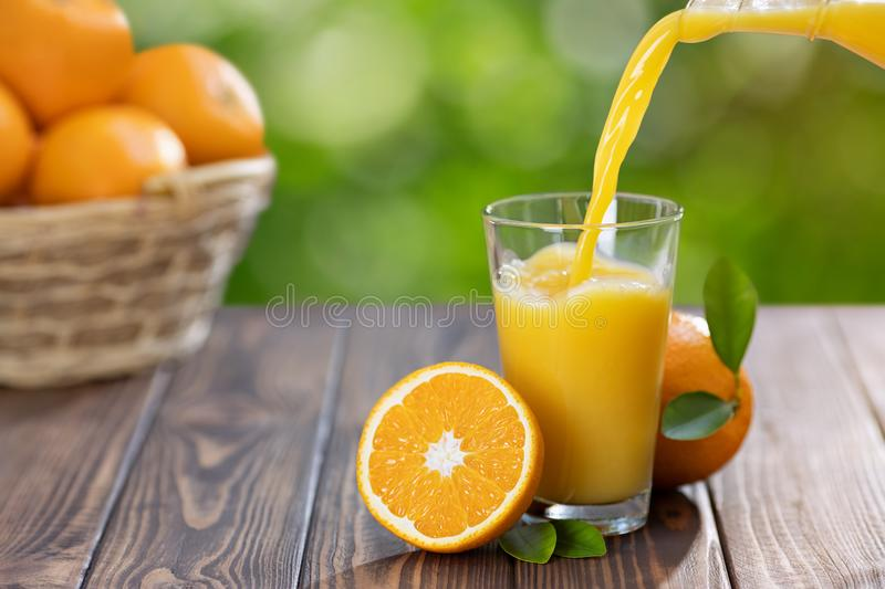 Orange juice pouring in glass royalty free stock photography