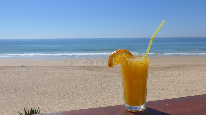 Orange juice, a refreshing, healthy drink on the beach with the sea view. Orange juice, a refreshing drink on the beach with the sea view royalty free stock photos