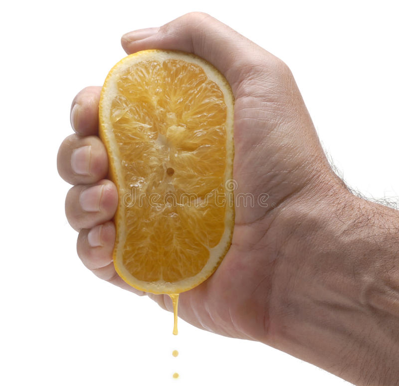 Orange juice squeeze : fresh orange half being squeezed by hand royalty free stock photography