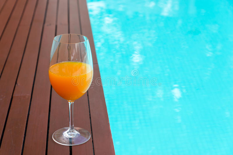 Orange juice in wine glass on edge the blue sky pool in party l. Uxury hotel, thailand stock image