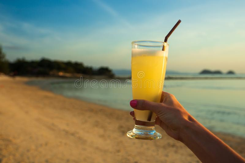 Orange juice in woman hands on the beach with sea background stock photo