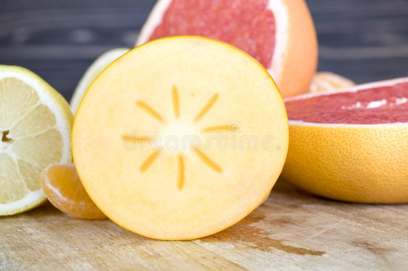 Orange juicy persimmon. Cut in half across, close-up of winter fruits royalty free stock images