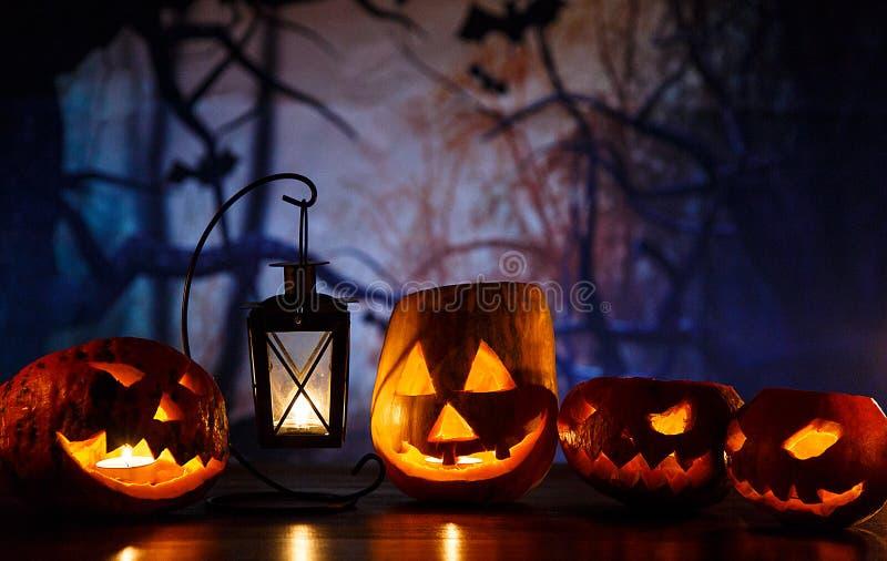 Orange Kürbise mit furchtsamen Gesichtern und Kerzen liegt auf dem Tisch vor dunkelblauem Hintergrund Halloween-Feier lizenzfreie stockfotos