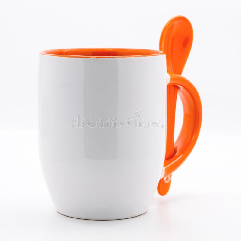 Orange kaffe rånar och skedar på moderna vita bakgrunder r royaltyfria bilder