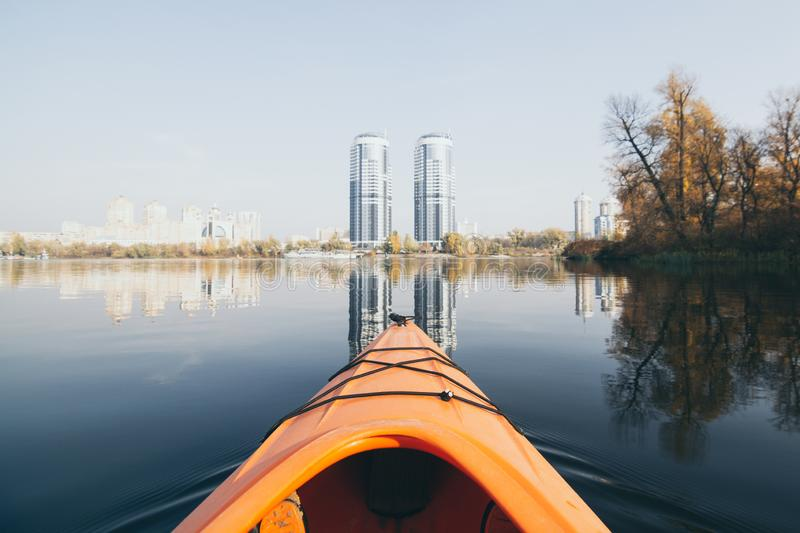 Orange kayak sailing towards modern buildings on the waters of Dnipro river in Kyiv, Ukraine. Orange kayak nose sailing towards modern buildings on the waters of royalty free stock photo
