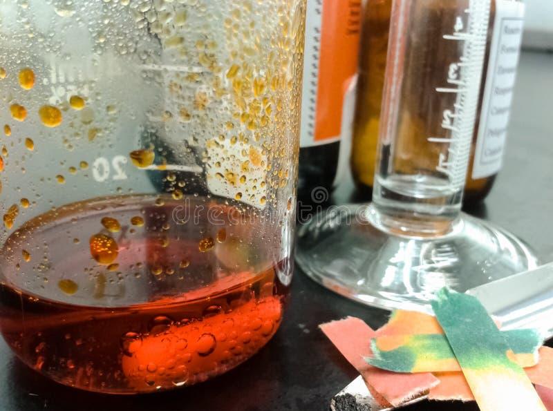Orange kemisk reaktion inom en exponeringsglasdryckeskärl royaltyfri foto
