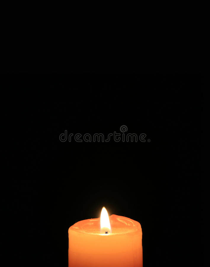 Orange Kerze, die auf dem schwarzen Hintergrund, vertikales Bild brennt stockfotografie