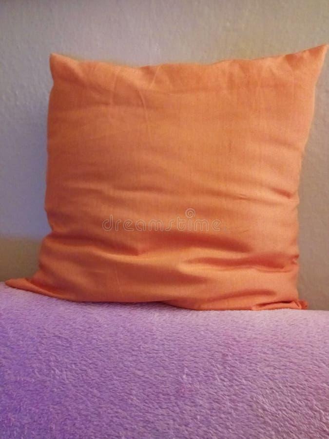 Orange Kissen auf der violetten Decke stockbild