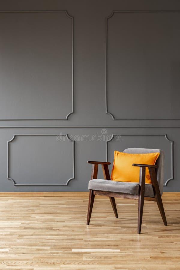 Orange Kissen auf hölzernem Lehnsessel in einfacher grauer Dachboden Innenwi stockfoto