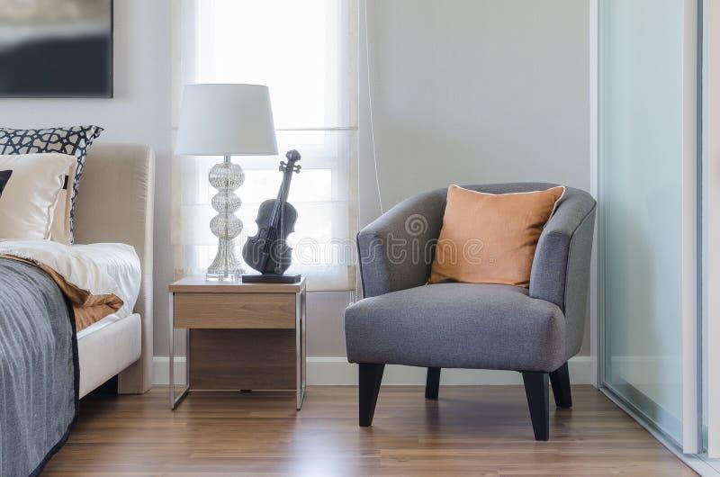 Orange Kissen auf modernem grauem Stuhl mit Nachttisch und Weiß stockfotos