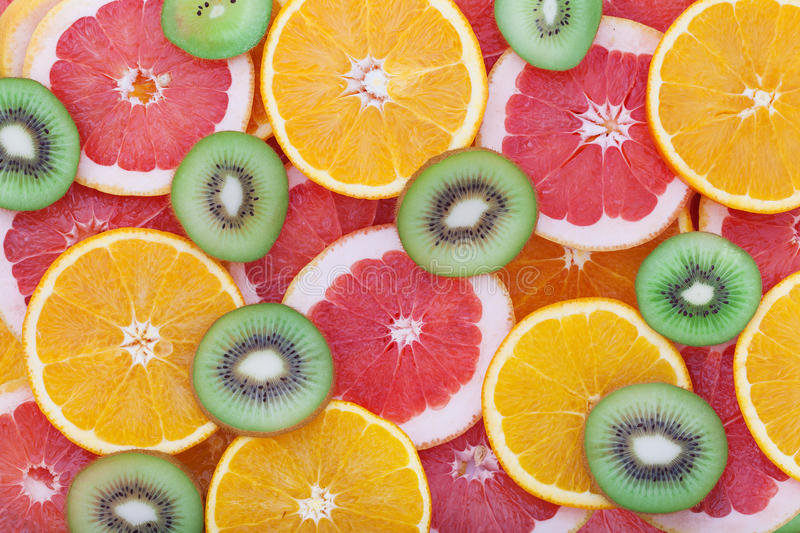 Orange, kiwi and grapefruit rings as background royalty free stock photo