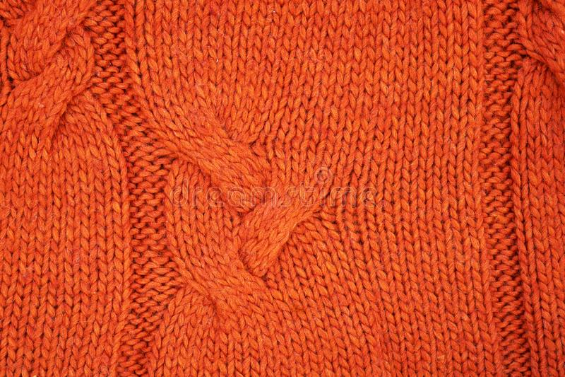 Red knitted texture with a relief pattern. Handmade Knitwear. Background, abstract stock images