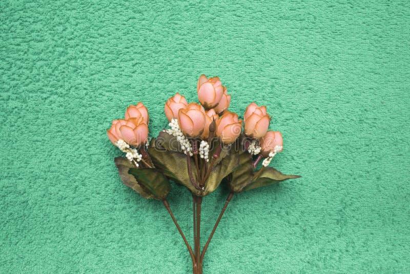 Orange konstgjorda rosor på mintkaramell-gräsplan bakgrund royaltyfria bilder