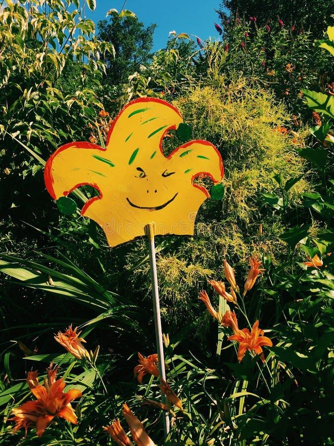 Orange kronaskulptur som står högväxt med växterna fotografering för bildbyråer