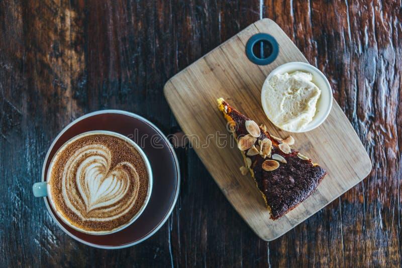 Orange Kuchen der Mandel mit Kaffeetasse lizenzfreie stockfotos