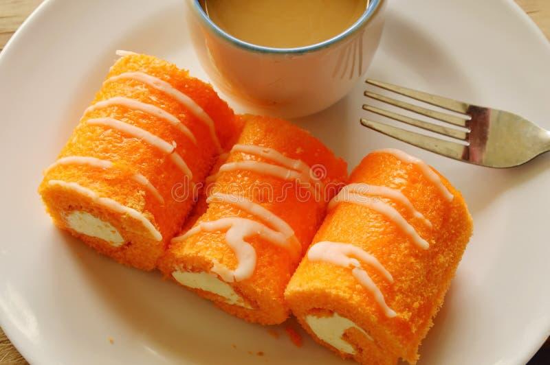 Orange Kuchenrolle füllte Creme und Kaffee auf Teller an stockbilder