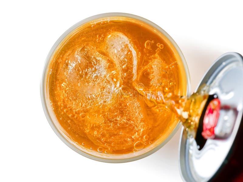 Orange läskflytande som häller från en can in i ett exponeringsglas överkant VI royaltyfri foto
