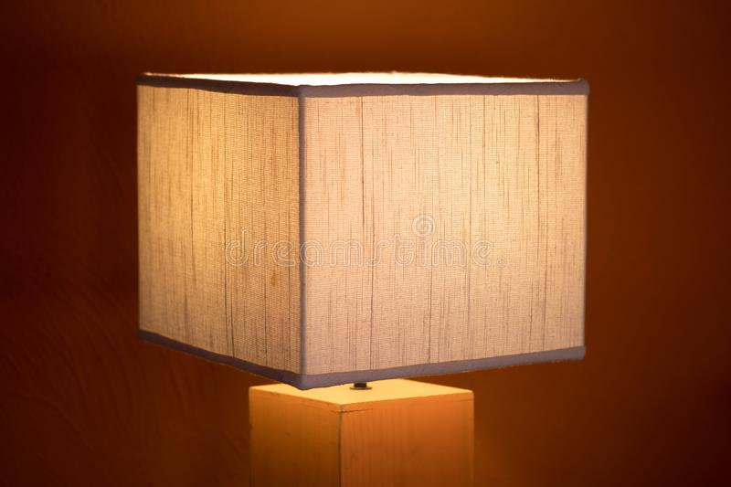 Orange lamp on a wooden dresser or a night table royalty free stock images