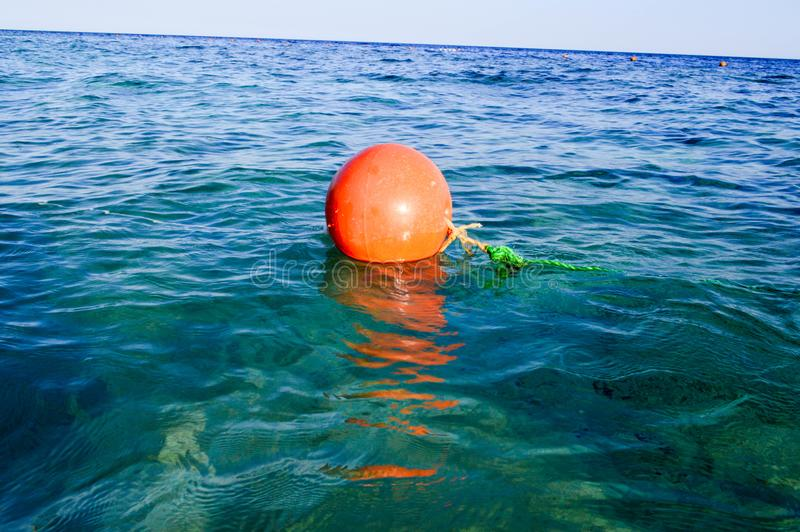Orange large round plastic rescue buoy floats in the blue salt sea for safety. royalty free stock image