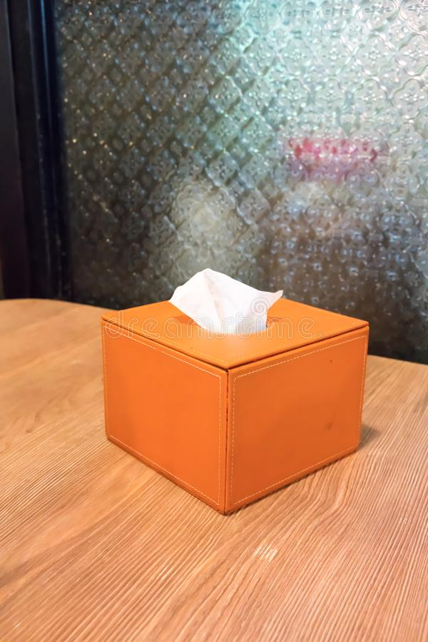 Orange leather cover tissue box on wooden table stock photos
