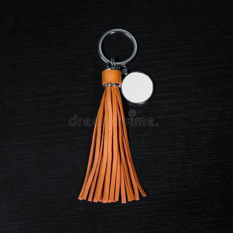 Orange Leather Tassel key ring on black wooden background. Fashion leather key chain for decoration. Orange Leather Tassel key ring on black wooden background stock images