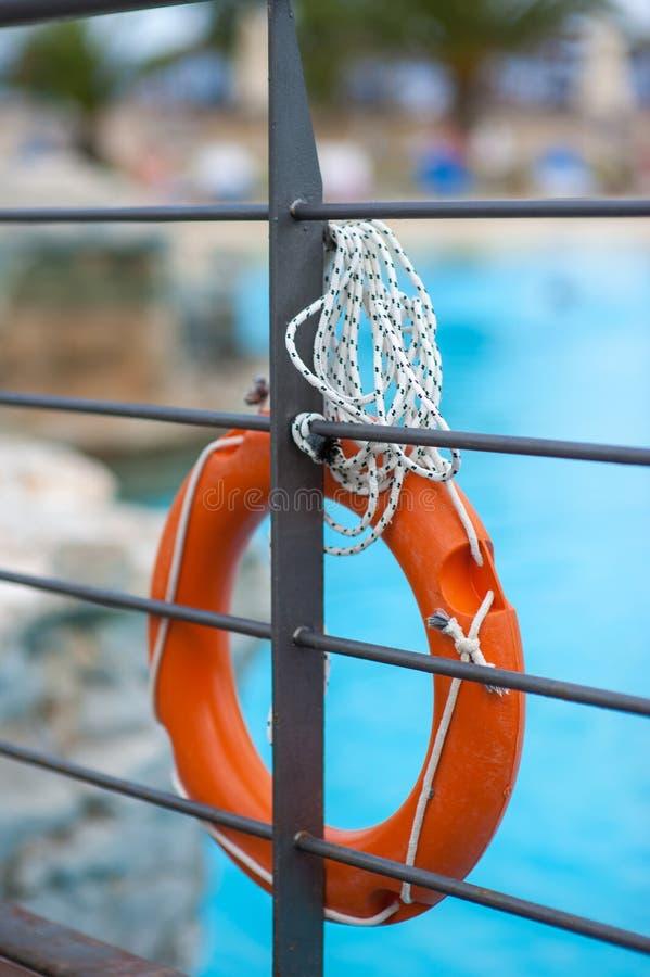 Orange Lebenboje mit Seil nahe dem Pool, das an der Brücke hängt stockfotos