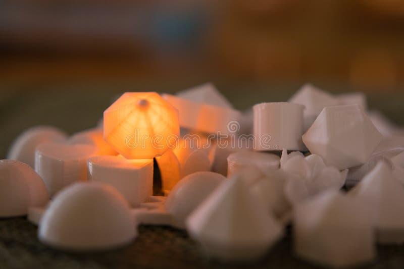 Orange LED diamond object nestled among other unlit objects royalty free stock photo