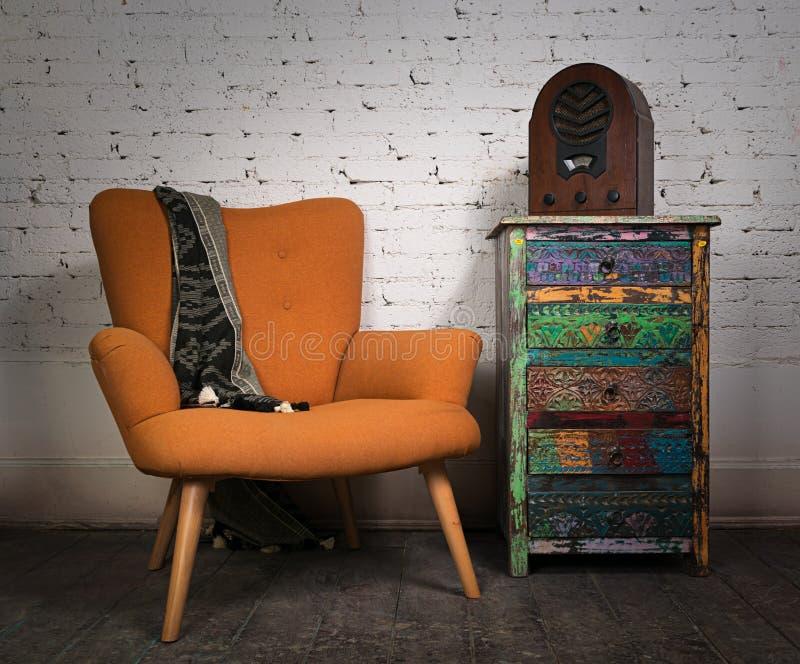 Orange Lehnsessel der Weinlese, bunter Schrank und gealterter hölzerner Radio stockfoto