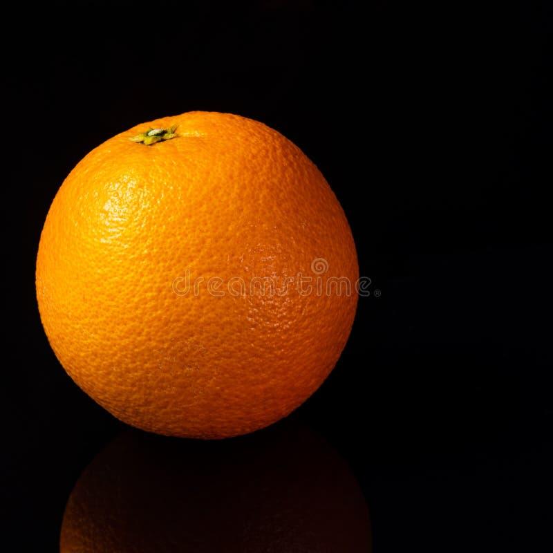 Orange liegt auf dem Tisch auf einem schwarzen Hintergrund lizenzfreie stockfotos