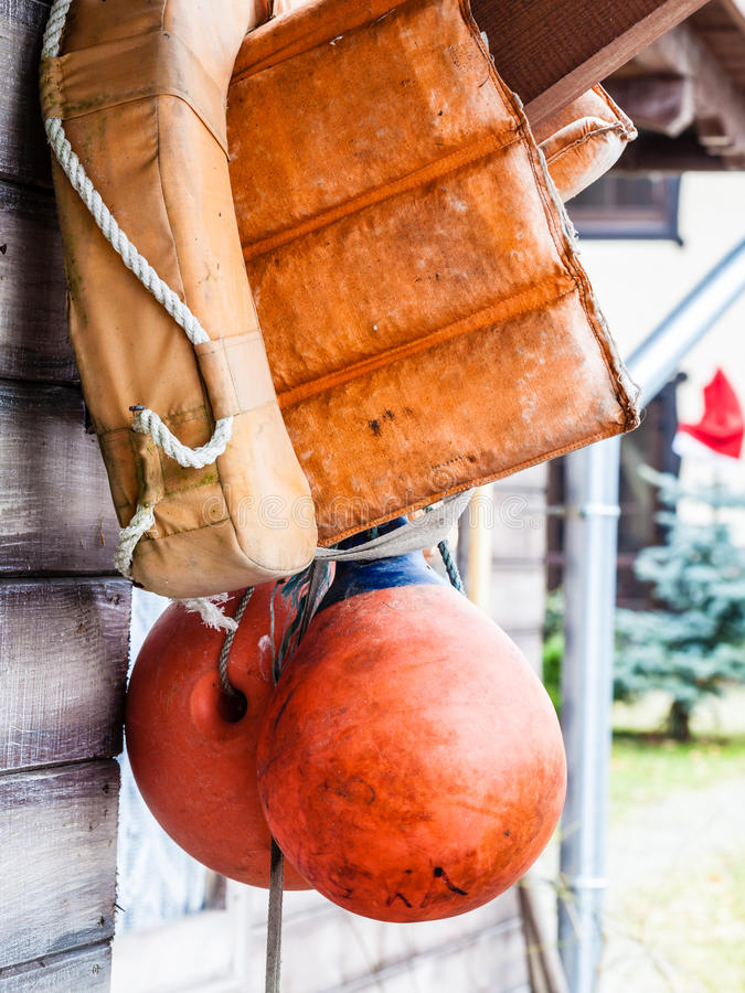 Orange life jacket and buoy hanging outside. Safety equipment concept. Orange life jacket and buoy hanging outside on wooden wall stock photography