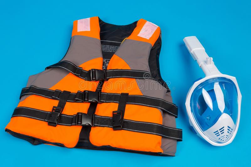 Orange life jacket and full face mask for diving, concept of diving and saving life in water. On a blue background stock image