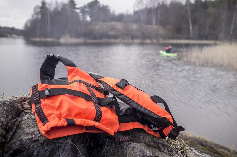 Orange life jacket lies on the rocky shore on the background of. A traveler is swimming in the kayak in the lake, overcast spring day royalty free stock image
