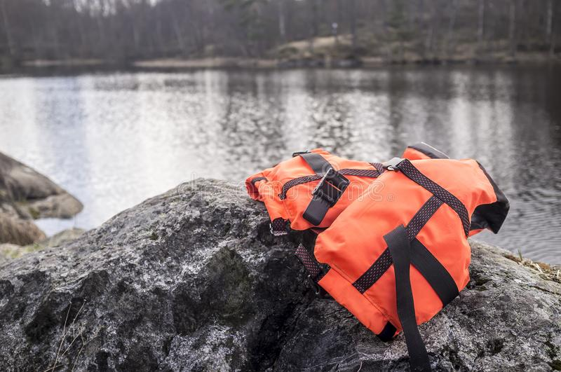Orange life jacket lies on the rocky shore of the lake in the ba. Ckground, cloudy day in early spring royalty free stock photo
