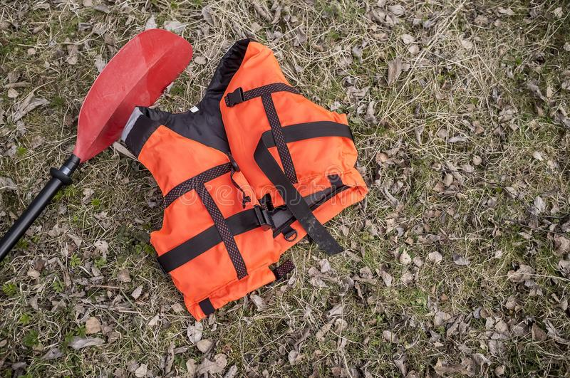 The orange life jacket and paddle lay on dry grass and old leave. S, early spring. Close-up royalty free stock photos