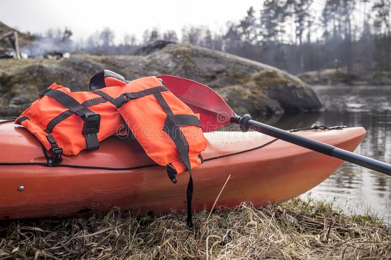 An orange life jacket and paddle lie on a kayak that stands on a. Borega of a lake, against a background of fire and rocks. Close-up stock photography