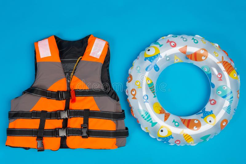 Orange life jacket and paddling inflatable circle for children, concept of summer and saving life on water. On blue background stock photo